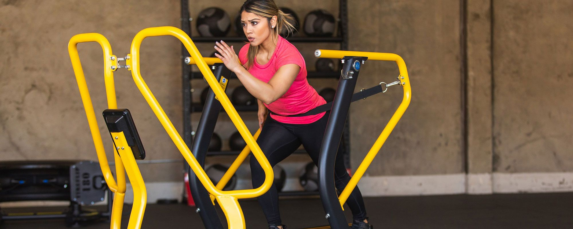 Woman using running resistance equipment in gym