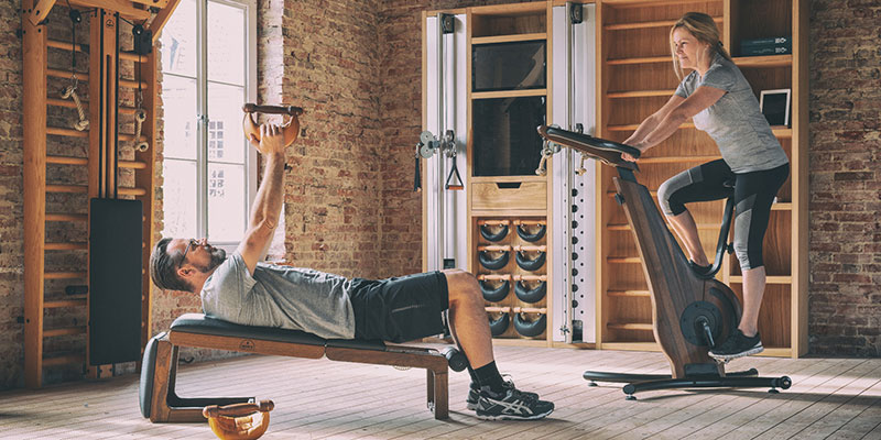 Man and woman using home gym